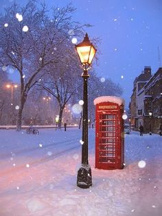Snowy street with lamp post and phone booth in Oxford, England