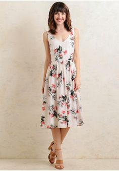 Ideal for Sunday brunch, this cream-hued midi dress is designed with a lovely floral print in hues of green, pink, and gray.
