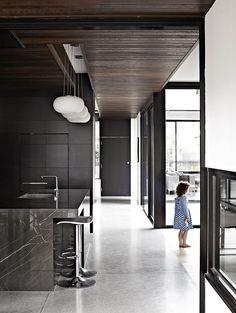 Black kitchen cabinets, black marble island, timber panelled ceiling, white pendant lights, grey polished concrete floor tiles