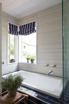 Crisp white, a walk-in shower and navy porcelain tile set a sleek modern tone in the spa-style master bathroom at HGTV Urban Oasis 2015.
