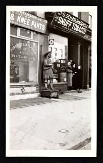 """8 x 10 print ofTwo storefronts:Horowitz & Greenbaum, mfrs of pants and knickers"""", andS. Scharlin & Son, mfrs of snuff tobacco .A group of people in winter coats stand on the stoop of S. Scharlin & Son."""