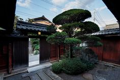The street and the front gate as seen from the entrance. Visitors enter the home through a sliding door—which is reddish-brown using traditi...