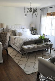 Fluffy white pillows, trays for books and easy to reach bedside lamps all from HomeGoods are accents that help guests feel right at home in this gray and white guest bedroom. (Sponsored pin)