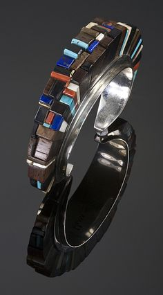 Sterling silver height bracelet by Charles Loloma.  Height inlay primarily of ironwood with Mediterranean coral, lapis, turquoise, fossil ivory and 14k gold accents.   Measures 5 1/2″ with a 1″ opening.  7/8″ width.