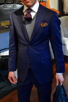 Men's Navy Blazer, Brown Pocket Square, Grey V-neck Sweater, White Dress Shirt, Burgundy Tie, Black Leather Briefcase, and Navy Dress Pants