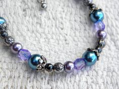 Purple and blue glass beads circle the wrist in a pattern of descending size, along with silver beads with rose designs and small, round hematite beads.