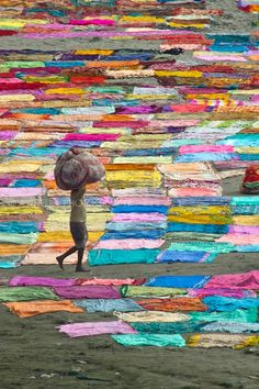 Boy carrying a load of laundry. Colorful saris drying on the ground
