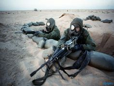 GIs in full chemical warfare suits man a forward position during Operation Desert Storm, 1991.