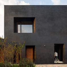 A matte-black rendering called Corev Mooth covers the walls of this residence, while window frames and shutters are made from a tropical tzalam wood coated in reddish sealer as a contrast.  Called Las Golondrinas, the house is composed of three volumes topped by a large sloped roof to create a covered patio that opens onto a swimming pool that aligns with the tree canopy. Black Walls, White Walls, Rendering Walls, Rendered Houses, Stone Deck, Building Foundation, Outdoor Walkway, Basement Floor Plans, White Oak Wood