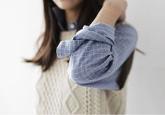 A very cute layered look with the button up blue shirt with the sleeves rolled up and a creme sweater on top.