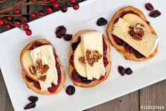 Crostini appetizers with cranberry sauce, apples, brie and pecans, above view on white plate
