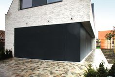 L-door sectionale garagepoort geïntegreerd in gevelbekleding met Renson lamellen | Realisatie: L-door | Ontwerp: Architect Wim Baekelandt Meer info? Surf naar www.cre-8-ive.be of www.l-door.be
