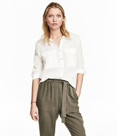 White. Long-sleeved, V-neck shirt in woven fabric with a collar. Buttons at front, chest pockets with flap, and yoke with pleat at back. Sleeves with
