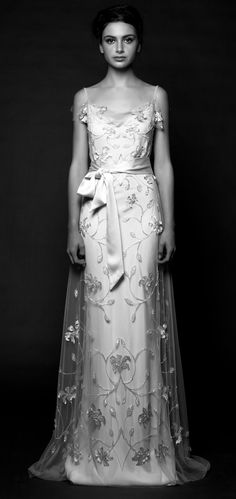 DAISY Trellised with laser-cut flowers and beaded floral motifs, this column wedding gown is a statement of feminine grace. A crepe silk slip
