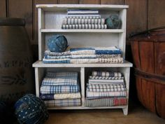 Jackie Cessna's vintage white doll cupboard...filled with old fabrics <3