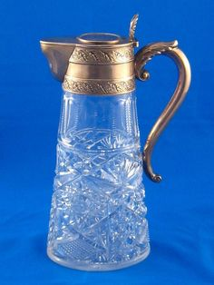 A Russian silver mounted cut glass claret jug circa 1880 with leaf capped scroll handle and scrolling leaf bands, the lid with acanthus thumbpiece and a coin of Catherine the Great dated 1734 inset. Ht.25cm ♥❦♥