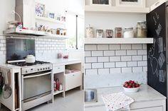 Una cocina predominantemente blanca, con cerámicos estilo 'Subway' en la alzada junto al artefacto de acero. En el mueble de madera, juego de cacerolas blancas de loza (Laura O), repasadores Liberty comprados en un viaje y más floreros repletos (ap Flores).  /Magalí Saberian