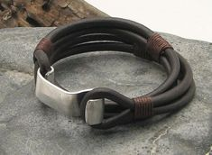 Handcrafted brown leather bracelet with hand hammered metal hook clasp and brown thread as accents. Combining the best of nautical with fashion design.