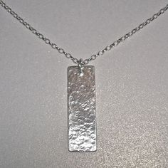 Sterling silver hammered rectangle drop pendant piece hung from a 45cm sterling silver belcher chain.