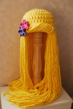 This is a Rapunzel-inspired wig. The hat is crocheted from chunky yellow yarn and the yarn hair is securely attached to the crochet stitches. Crochet For Kids, Crochet Baby, Knit Crochet, Crochet Wigs, Crochet Beanie, Knitted Hats, Crochet Crafts, Crochet Projects, Kids Wigs