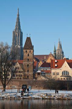 """Ansicht Ulm, Metzgerturm, Rathaus, Münster  Im spätwinterlichen Gewand präsentiert das Kalenderbild Februar die Donauansicht der Stadt mit Münstertürmen und Rathausgiebeln, die den Metzgerturm hinter der Donaustadtmauereinrahmen; symbolisiert ist so die einstige Reichsstadt mit ihrer Pfarrkirche, mit ihrer politischen Mitte und mit ihrer Befestigung: """"Stadtluft macht frei""""!     1480 bauten die Ulmer hier ihre neue Stadtmauer, damals noch"""