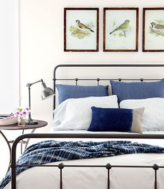 For the guest room of this California home, the homeowner selected a Wisteria nightstand and a hand-forged iron bed frame by Charles P. Rogers. The trio of aviary prints is from the Encinitas furnishings store Rustic Rooster.   - CountryLiving.com