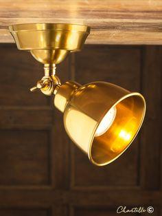 Antique brass spotlight with adjustable head.