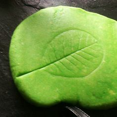Playdough meets nature with leaf prints in dough.