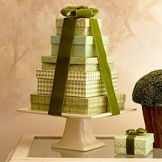 Cake plates seldom get used steadily so put one to work in your Christmas display. Lidded boxes wrapped in coordinating scrapbook papers and stacked from largest to smallest make their grand stand on a square cake pedestal. Pretty velvet ribbon pulls it all together.