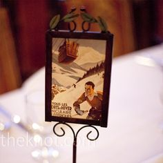 Iron frames displayed vintage ski postcards on each table with the table numbers in the wedding colors attached.