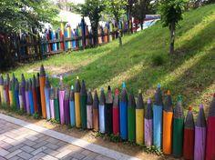 clôture de jardin avec décoration créative en crayons géants multicolores