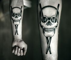 Skull with drum sticks tattoo