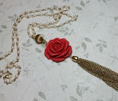 This beautiful red rose tassel necklace is the perfect mix of boho and vintage. A long vintage brass chain tassel dangles below a deep red clay rose accented with a pretty goldtone bead. The necklace length is approximately 30 long and closes with a lobster clasp. The drop length