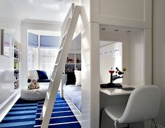 Peter Pennoyer Architects    white & blue modern boy's bedroom design with white bunk beds, desk area, white & blue striped rug, white ladder, white pouf, blue roman shades, bay window with bright blue cushion and built-ins.