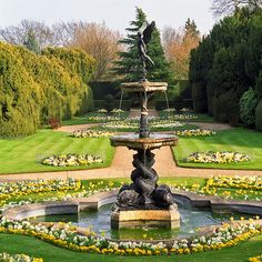 Ascott House Gardens, Buckinghamshire, UK | A view of the Eros (Cupid) Fountain with a bedding scheme in a formal garden (17 of 22)