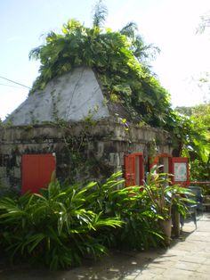 Golden Rock, a restaurant and hotel - old building in cut stone. Old cottages amongst lush, green foliage and flowers in Nevis
