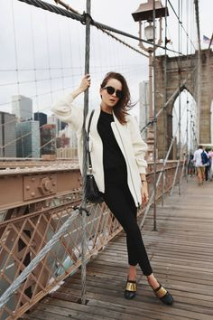 Fashion blogger and IT girl Andy Torres from StyleScrapbook standing on the Brooklyn Bridge with New York City in the background