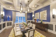 This Hamptons Showhouse has dark wood flooring, an ornate wainscot, bright blue walls, silver and white ceiling, simple dining table with white chairs and a bight patterned area rug.