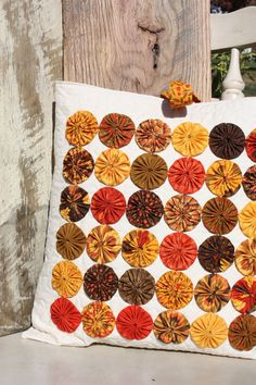 Oh, the deep deep rich colors of Fall! The leaves are changing here in Middle Tennessee and this quilted Yo-yo Pillow cover reminds me of all