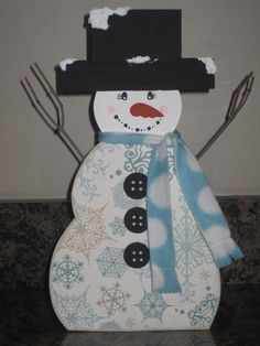 """I love making things at Christmas time for our neighbor gifts. This will be for this year, 2012. It's about 12"""" tall. I got the snowman wood at Wood Connection, the grapevine and the wood to build the hat at Michael's Crafts and the scarf fabric at Joanne's Fabrics. I cut the wood for the hat and drilled holes in the sides of the snowman for the arms to go in. It really didn't take too much time, and I love how it turned out."""