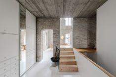 Hamburg studio Asdfg Architekten has converted a 19th-century miller's house in Berlin into a modern family home arranged around original brick walls
