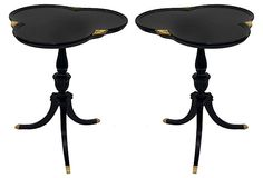 Beautiful pair of cloverleaf tables, lacquered in black with hand-painted gold accents and brass capped feet.