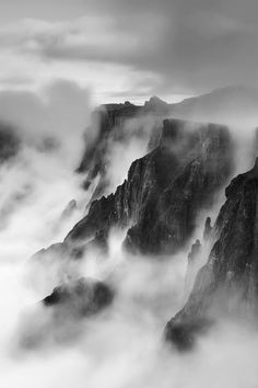 Landscape photograph of mist swirling up the amphitheater wall blurred by a long exposure, drakensberg, south africa
