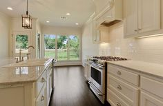 Cream and River White Granite. White subway tile.  the hardwood grounds the space