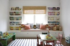 Adorable playroom design with white built-in window seat.