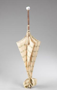 """1880s. """"One of the fashionable features of this parasol is the ball handle, which was one of the most popular styles in the 1880s. Also, this parasol would function well as a sunshade in addition to being a decorative accessory."""" metmuseum.org"""