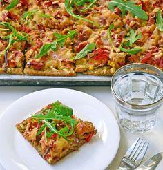 Pizza topped with pesto, chicken and serrano ham