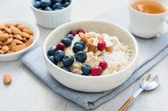 Oatmeal porridge bowl with blueberries, cranberries and almonds and cup of green tea. Concept of healthy lifestyle, healthy eating, fitness menu and dieting Oatmeal Porridge, Breakfast Porridge, Eat Breakfast, Rice Berry, Cooking Recipes, Healthy Recipes, Rice Recipes, Queso Fresco, Lean Protein