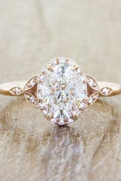 An Oval Diamond Engagement Ring With Leaf Shoulders And Gold Band Sits On A Wooden Table Rose Gold Engagement Ring, Halo Engagement, Vintage Engagement Rings, Vintage Rings, Timeless Engagement Ring, Unique Vintage, Intricate Engagement Ring, Country Engagement, Vintage Stil