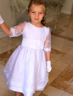 A dress to remember always. Finely embroidered sleeves and skirt of tulle over taffeta girls dress with structural petticoat for a full skirt. Separate taffeta sash with optional monogram.